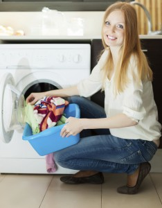 Long-haired blonde woman using washing machine at home